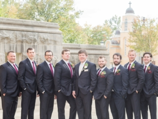 Groom with groomsmen in dark suites with wine color ties and boutineers captured by Ryan and Alyssa Photography