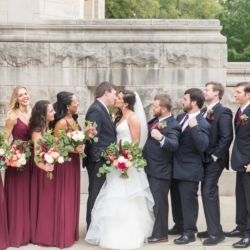 Bridal party picture as bride and groom embrace, shows bridesmaids in beautiful wine color dresses holding hand tied bouquets designed by Magnificent Moments Weddings