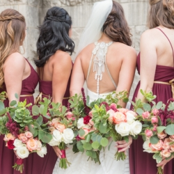 Charlotte bridal party showing off the back of their gowns bridesmaids dressed in wine colored dresses with hand tied bouquets designed by Magnificent Moments Weddings