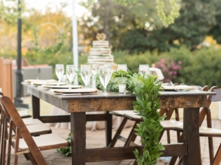 Outdoor wedding reception farmhouse tables and chairs rented from Party Reflections with long greenery runner designed by Magnificent Moments Weddings
