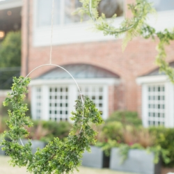 Wedding reception decor hanging hoops accented with greenery captured by Ryan and Alyssa Photography