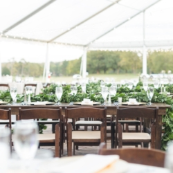 Outdoor wedding reception at Carmel Country Club with dark wood farmhouse tables and chairs rented from Party Reflections set with long greenery garlands designed by Magnificent Moments Weddings