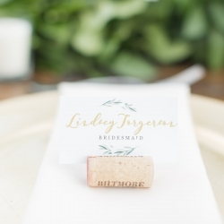 Calligraphy designed escort cards placed in wine cork detail shot captured by Ryan and Alyssa Photography