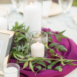 Wedding centerpieces made of pillar candles placed ontop of wine color fabric with accent greenery