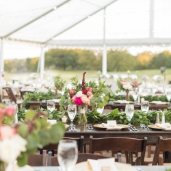 Outdoor wedding reception under clear top tent with dark wood farm house tables rented from Party Reflections