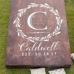 Wedding cocktail hour games of corn hole with custom cornhole board with wedding crest reception held at Carmel Country Club in Charlotte North Carolina