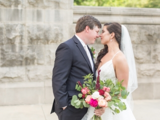 Bride and groom embrace after wedding ceremony bride holding hand tied bridal bouquet filled with pink and wine colored flowers accent with greenery designed by Magnificent Moments Weddings