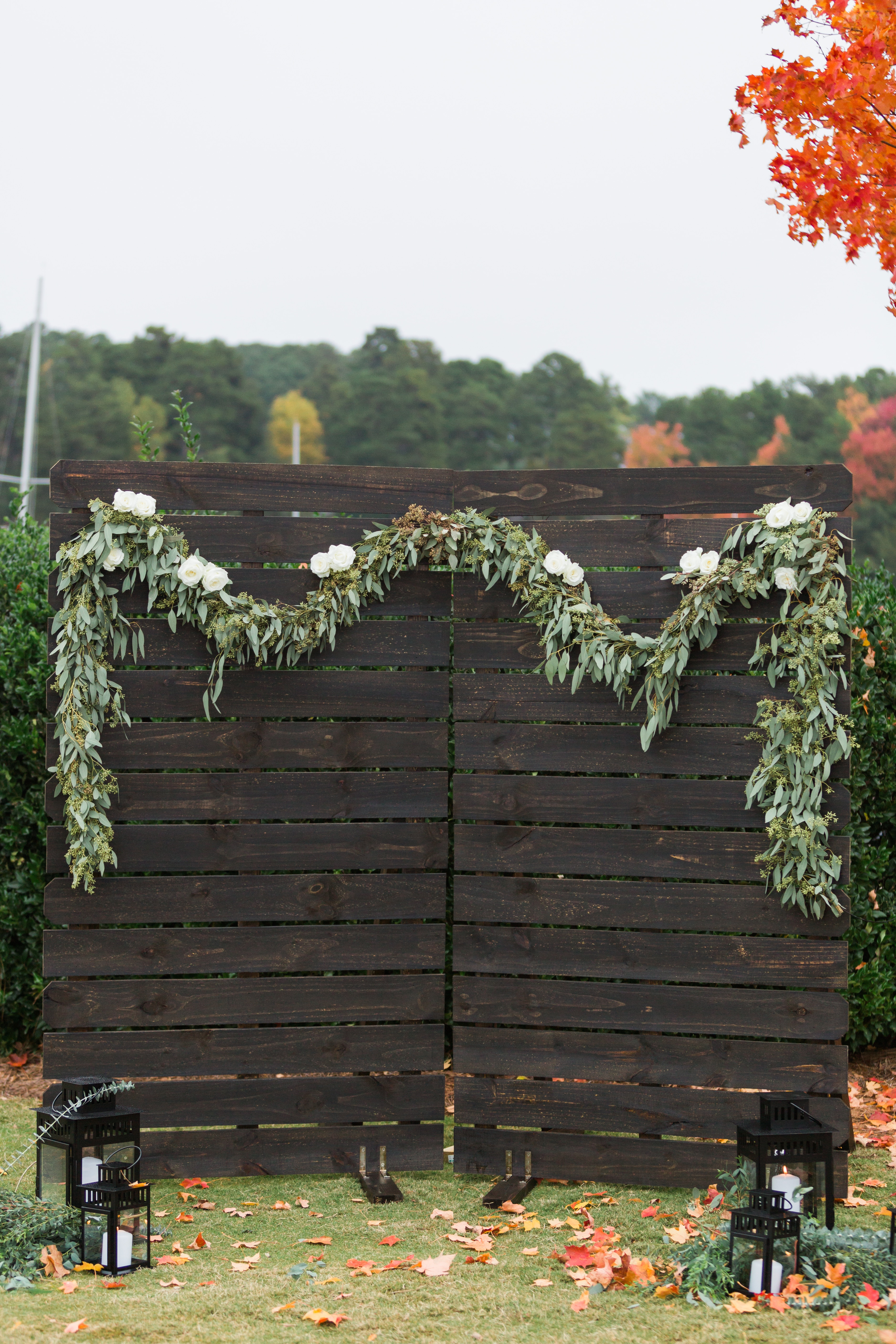 Wedding alter of wooden palettes draped with greenery and florals designed by Magnificent Moments Weddings for an outdoor fall wedding in Charlotte North Carolina