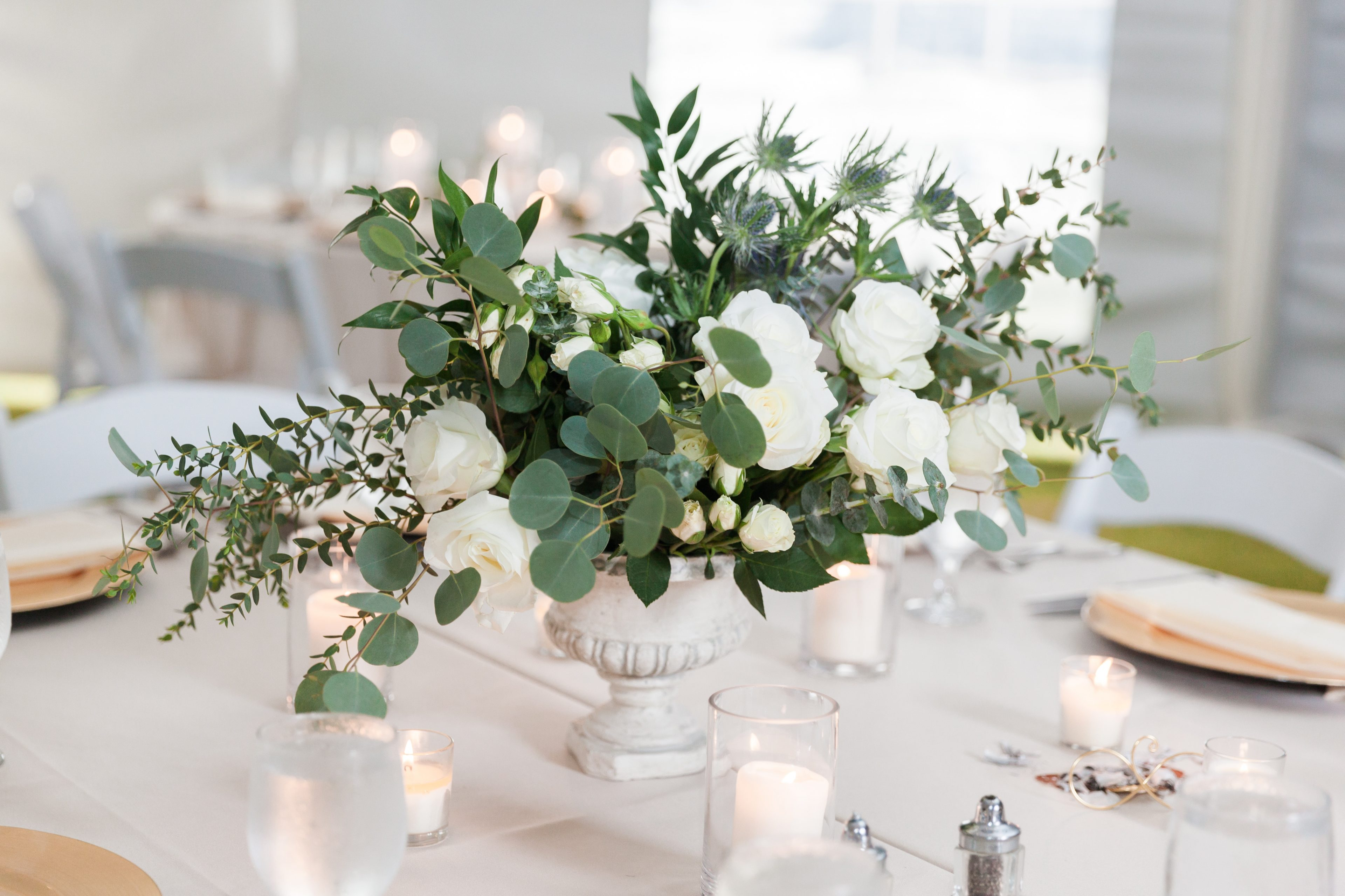 White column vase wedding centerpiece filled with greenery and white roses