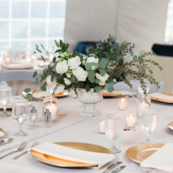 Wedding reception tablescape, gold chargers, ivory napkins, set off by white vase centerpiece with greenery and white roses created by Magnificent Moments Weddings