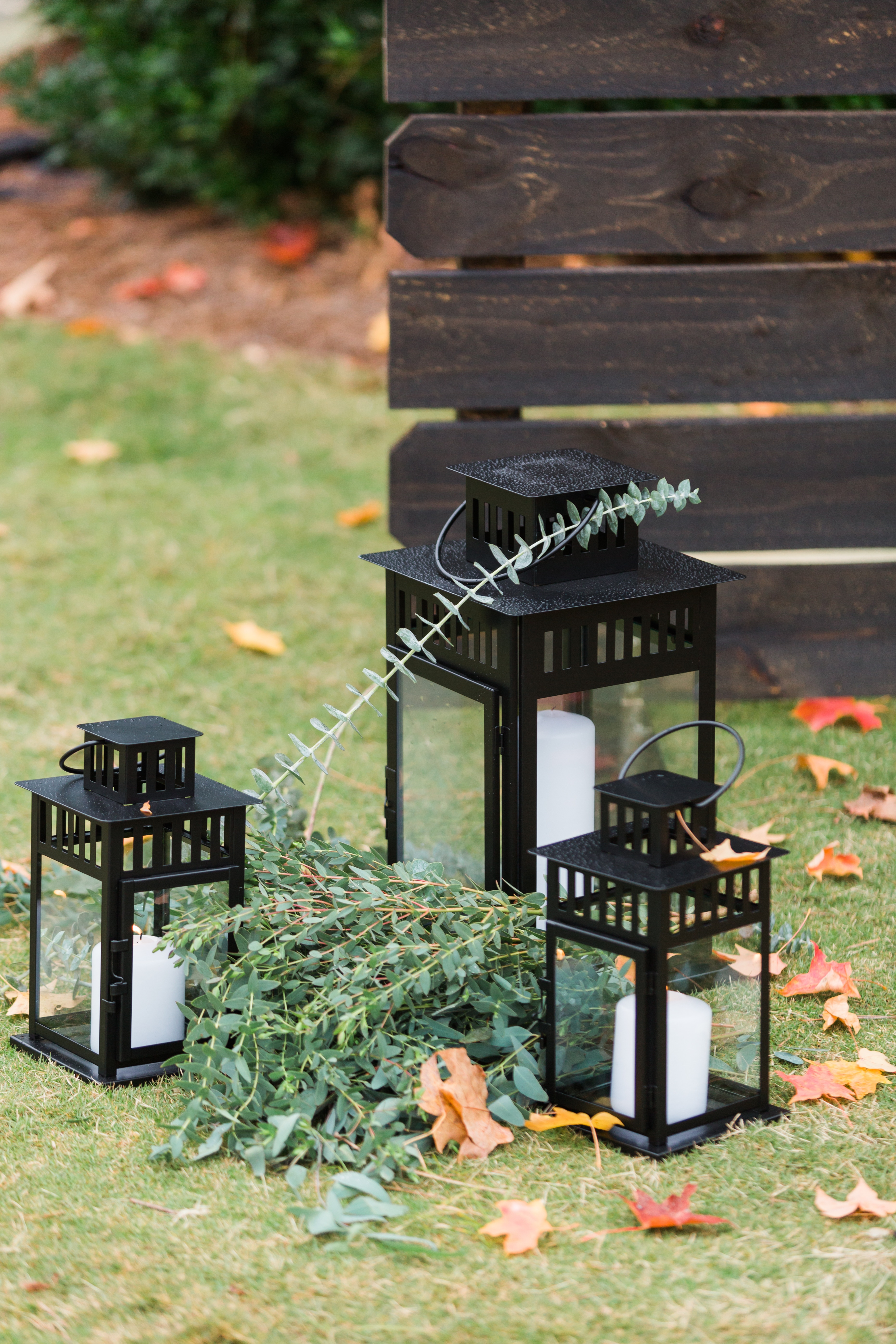 Black lanterns anchor the ceremony space at an outdoor fall ceremony in Charlotte North Carolina