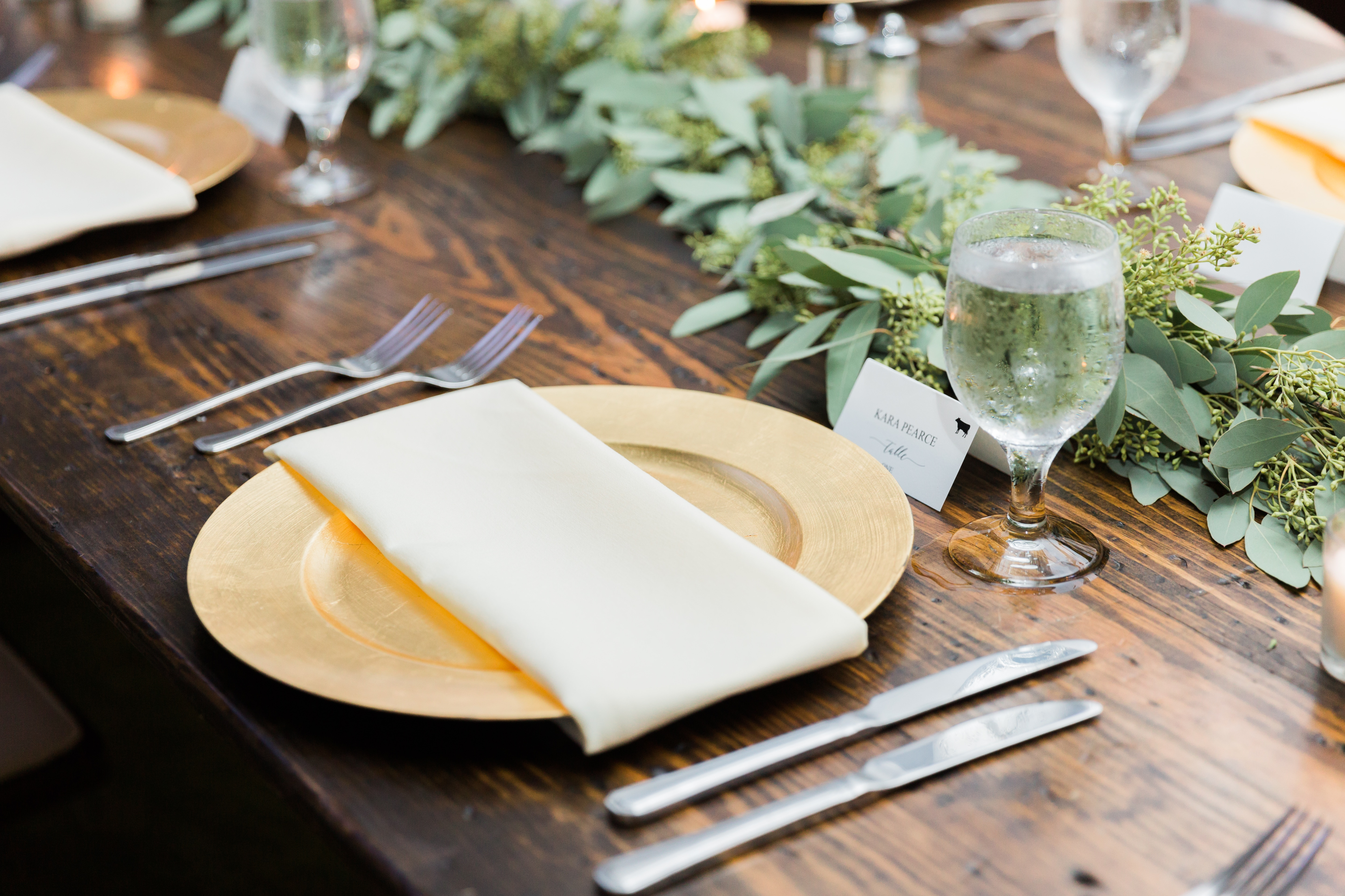 Wedding tablescape, gold charger, ivory napkins, green garland by Magnificent Moments Weddings, farmhouse table rented from Party Reflections