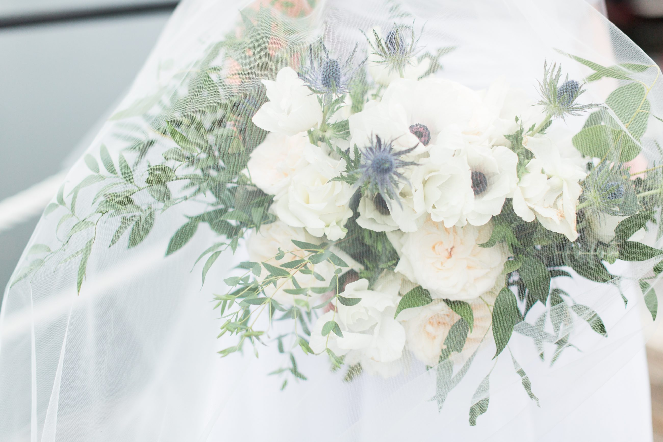 Bridal bouquet simple white flowers with greenery in a hand tied design by Magnificent Moments Weddings