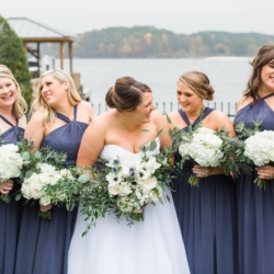 Bridal party in blue bridesmaids dresses with hand tied white hydrangea bouquets