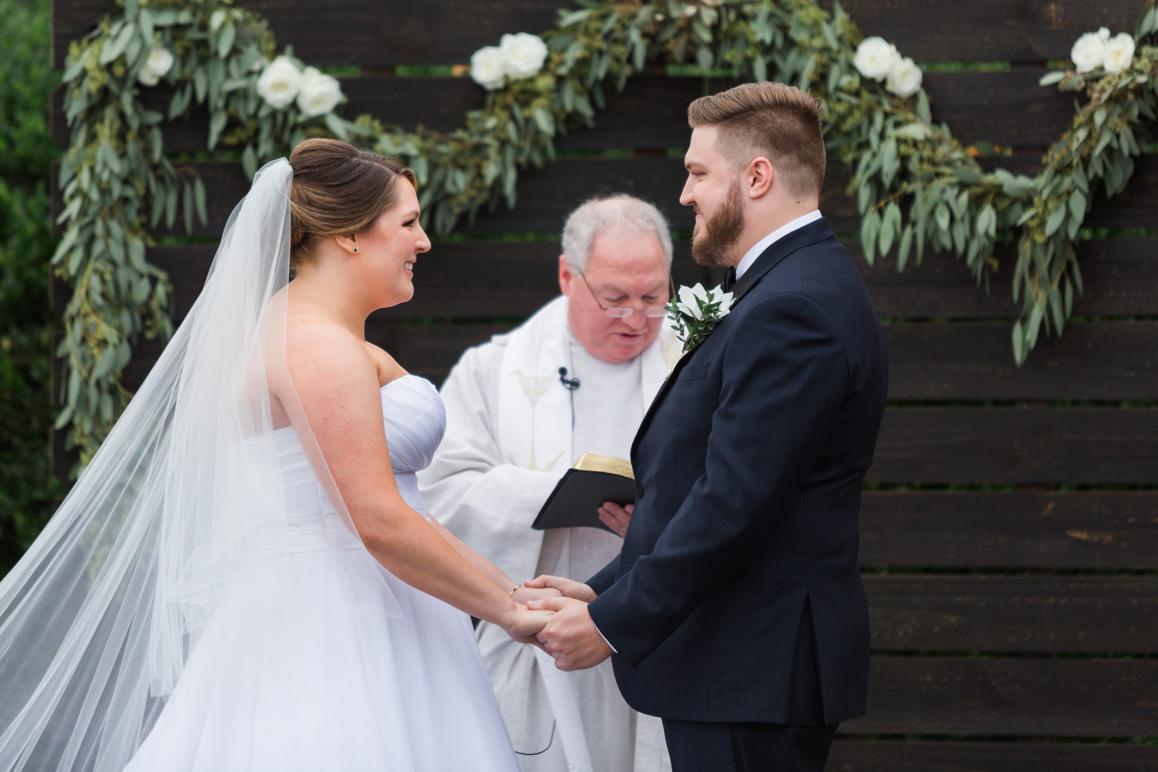 Ceremony vows between bride and groom in front of a wooden palette alter peice with florals designed by Magnificent Moments Weddings