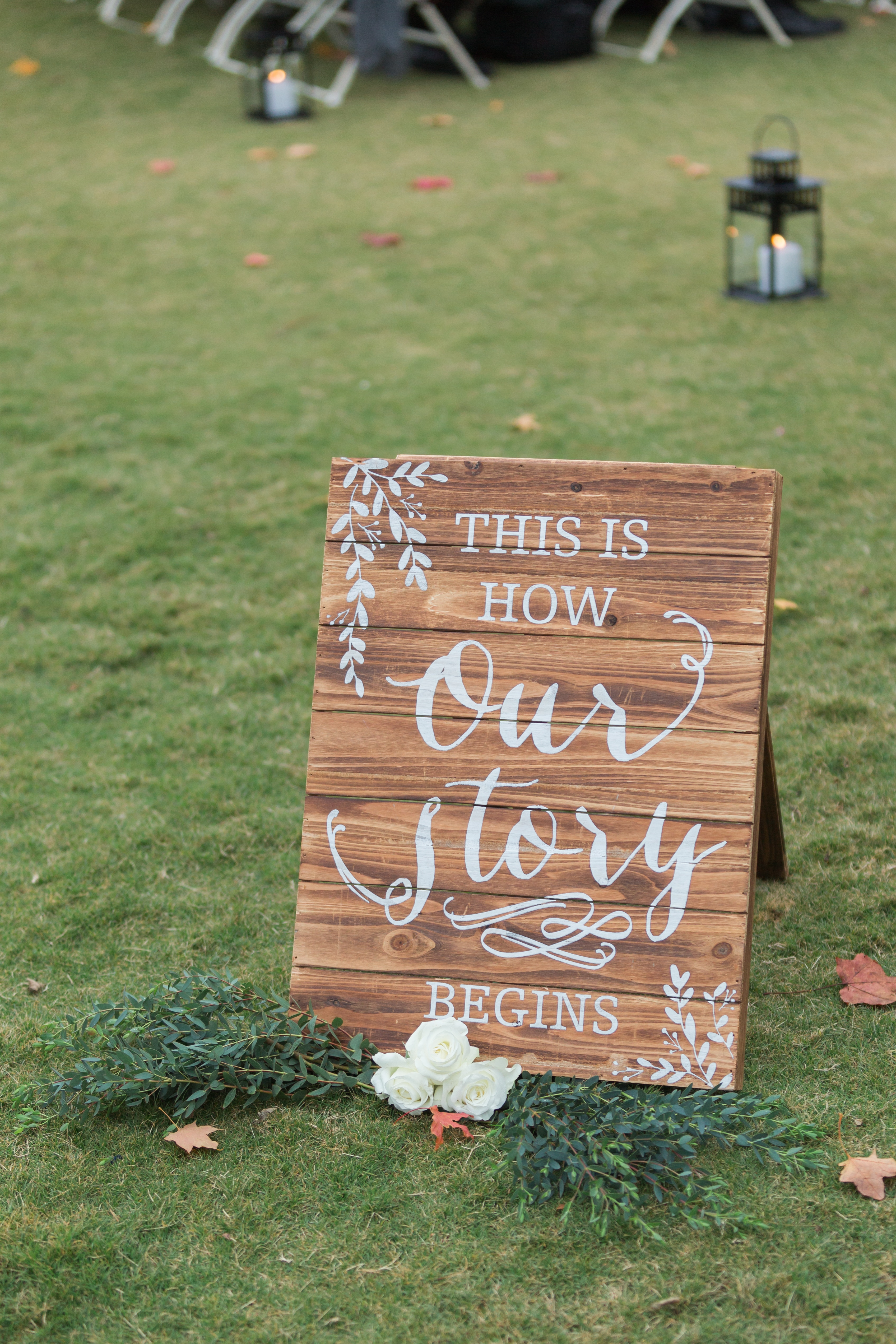 Wedding welcome sign accented with greenery and white roses ceremony outdoors at Peninsula Yacht Club
