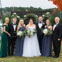 Wedding party family photo with bride and groom outdoor ceremony backed by palate wood with greenery and roses