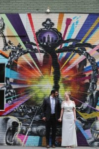 Bride and groom pose in front of urban art on the streets up Uptown Charlotte