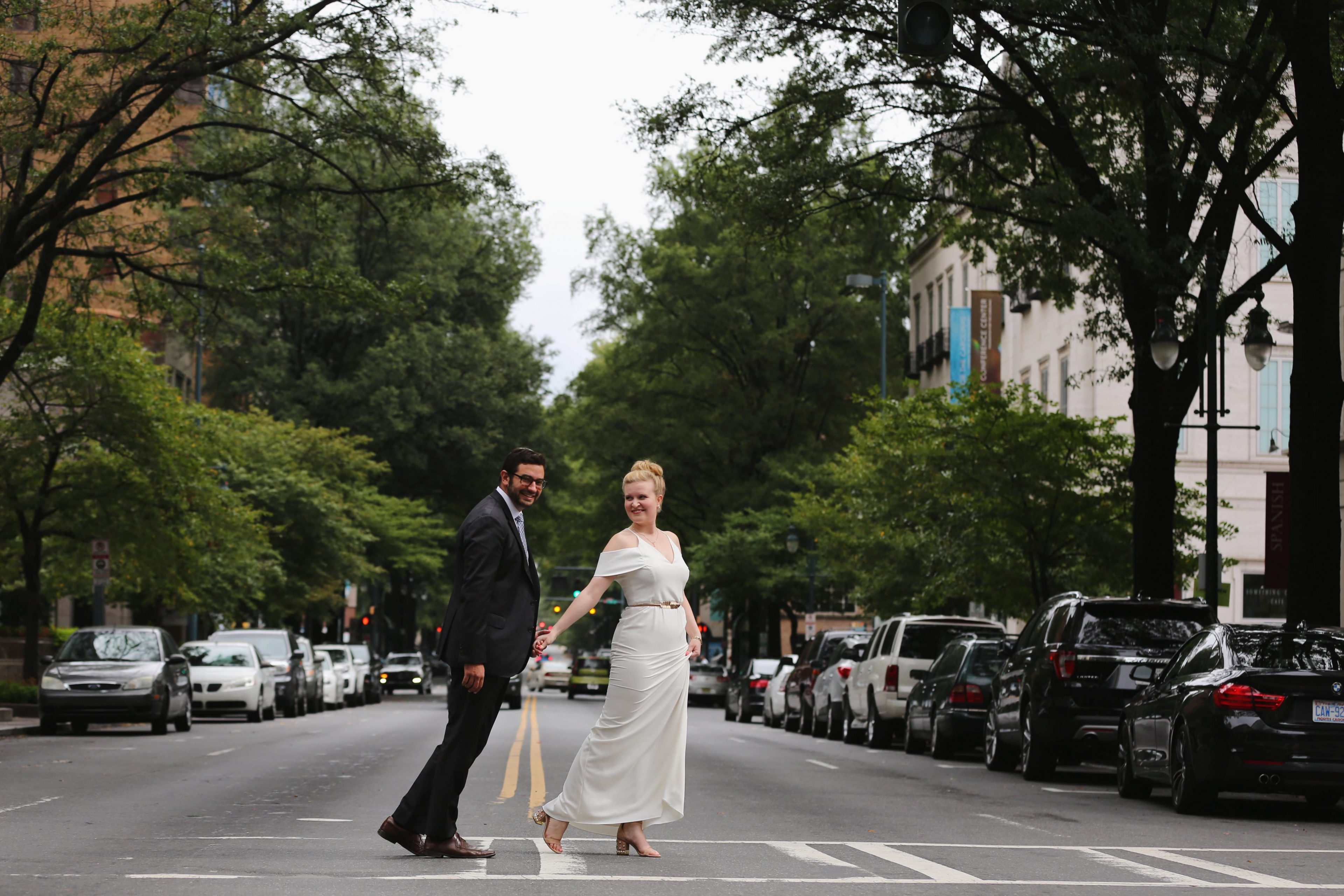 Bride and groom walk hand in hand for bridal portraits in Uptown Charlotte