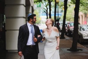 Bride and groom pose on Charlotte city street while bride wears a white off the shoulder gown