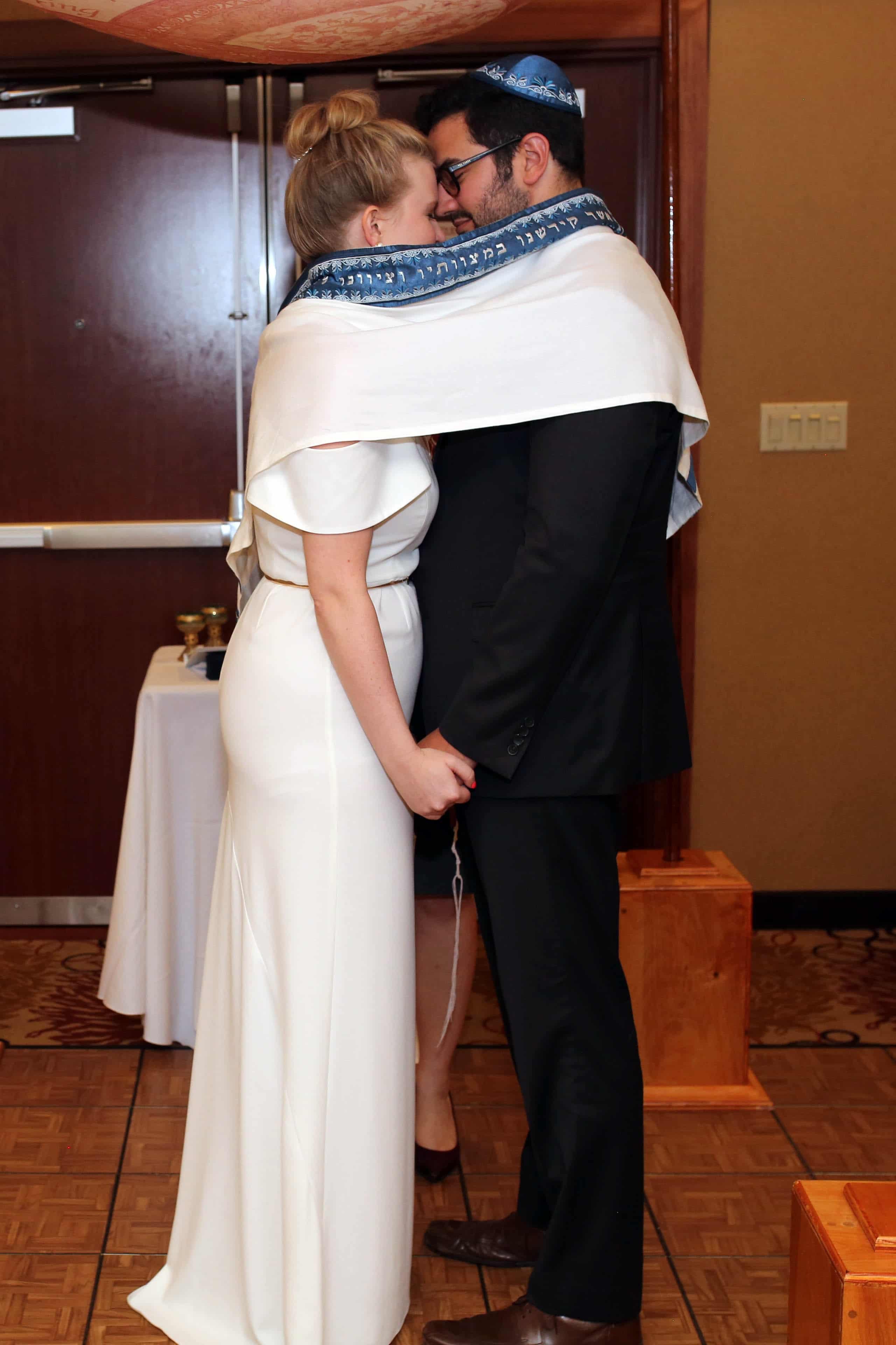 Bride and groom celebration traditional Jewish aspects of their Uptown Charlotte wedding coordinated by Magnificent Moments Weddings