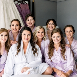 Bride poses with her bridesmaids wearing matching robes while being pampered by Cali Stott Artistry
