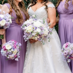 Bride poses with bridesmaids who hold stunning bouquets of soft spring colors created by CLux for a spring wedding at Foundation for the Carolinas