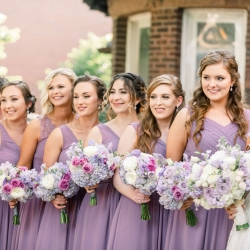 Bride poses with her bridesmaids all wearing soft lavender dresses and holding stunning bouquets created by CLux