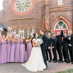 Bride and groom share a sweet moment with their bridal party as they cheer on the Newly Weds in Uptown Charlote