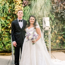 Bride and groom stand in the gardens of Foundation for the Carolinas during their spring wedding captured by Sunshower Photography
