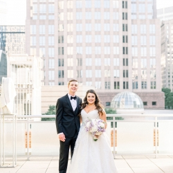 Sunshower Photography captures a bride and groom amid the Charlotte Skyline as they prepare for their Uptown Charlotte Wedding