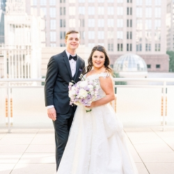 Bride and groom are all smiles as they pose among the skyscrapers of Uptown Charlotte on their wedding day