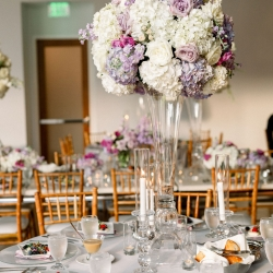 Stunning floral centerpieces by Clux featured white hydrangeas and soft lavender hues in stunning glass vases