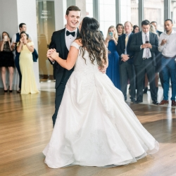 Bride and groom share a first dance as guests onlook during their spring wedding coordinated by Magnificent Moments Weddings