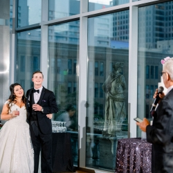 Bride and groom listen to touching toasts from friends and family during a wedding reception coordinated by Magnificent Moments Weddings