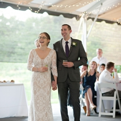 Bride and groom are all smiles as their family toasts them and their new life during a reception coordinated by Magnificent Moments Weddings