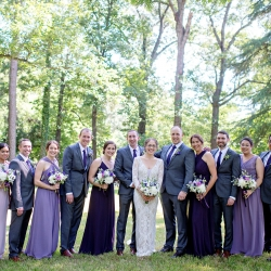 Bride and groom pose with their bridal party all sporting hues of purple perfect for a spring garden wedding in Lancaster, South Carolina