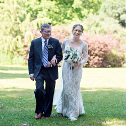 Bride is escorted down the aisle by her father to her awaiting groom in the gardens of the Ivy Place during a sweet spring wedding