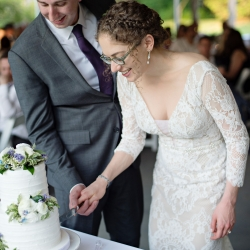 Bride and groom cut their cake during their wedding reception planned and coordinated by Magnificent Moments Weddings