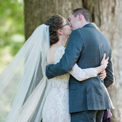 Bride and groom share a kiss after exchanging vows during their garden wedding at The Ivy Place