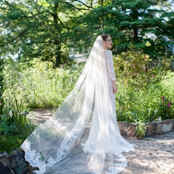 Brides stunning veil features lace details that complement her lace dress perfect for a garden wedding