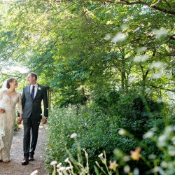 Bride and groom walk hand in hand through the gardens of The Ivy Place for their spring South Carolina wedding