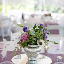 Striking silver vases held beautiful centerpieces that showed of spring colors of purples and blues for a garden wedding at The Ivy Place