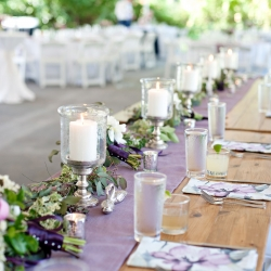 A rustic farm house table set the tone for a garden head table that featured floral napkins and lavender runner rented from BBJ Linens for a spring wedding at The Ivy Place