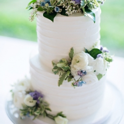 Simple two tier white cake features soft white flowers with accents of blues created by Wow Factor Cakes for a spring wedding at The Ivy Place