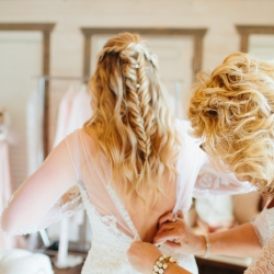 Brides mother helps button her dress as she prepares for her mountain top wedding ceremony coordinated by Magnificent Moments Weddings