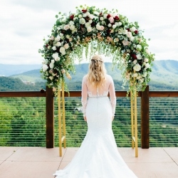 Bride shows up the back of her stunning dress under a floral arch in the Tennessee Mountains at The Magnolia Venue