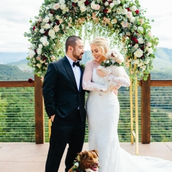 bride and groom pose with their dogs who are sporting custom floral collars during their fall wedding coordinated by Magnificent Moments Weddings