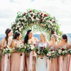 Bride poses with her bridesmaids under a stunning floral arch covered in roses created by LB Florals