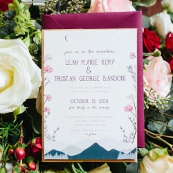 Stunning wedding invitations feature the lush mountain ranges that housed the couples unique wedding venue